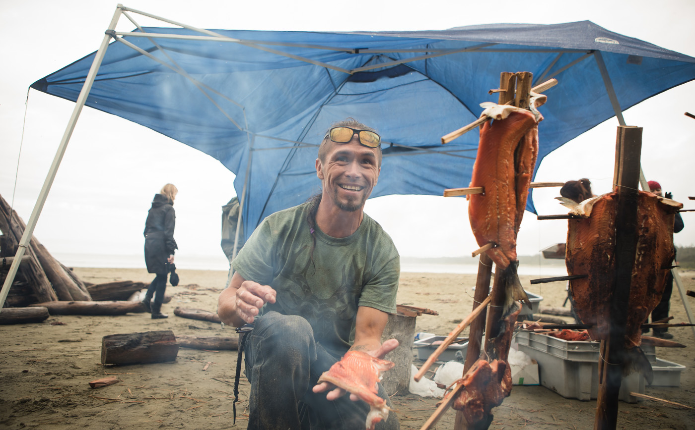 A man holds a piece of smoked fish on a beach.