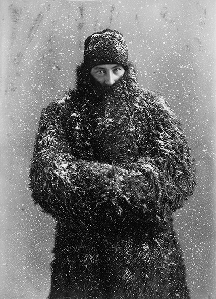 Black and white picture of man in fur hat and coat.