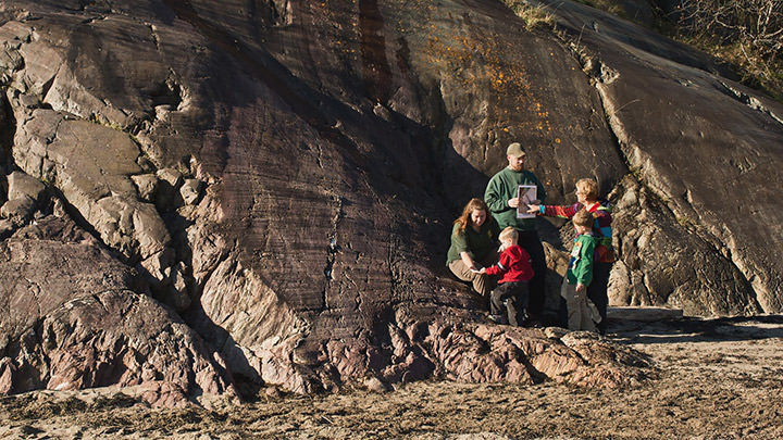 Guides from the Stonehammer Geopark in New Brunswick explain the history of the geological site to visitors.